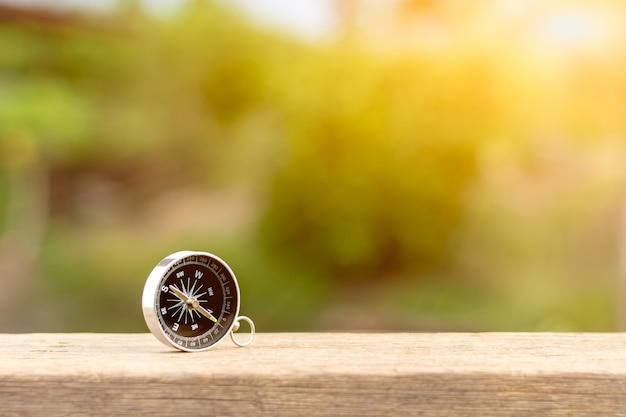 Boussole sur le bureau en bois dans la matinée. - pour concept voyageur