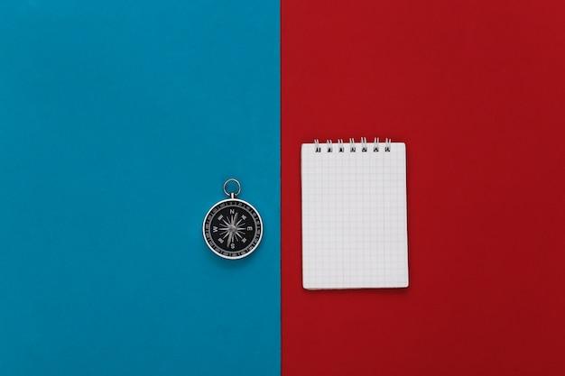 Boussole et cahier sur un rouge-bleu. planification de voyage