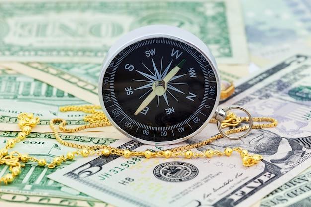 Boussole et collier en or sur les billets en euros euro et dollars
