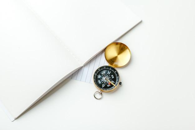 Boussole dorée avec bloc-notes et stylo noirs se bouchent sur une table