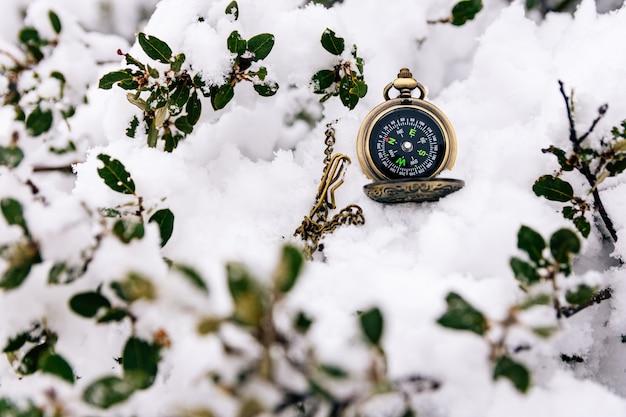 Boussole dorée perdue dans la neige. paysage enneigé.