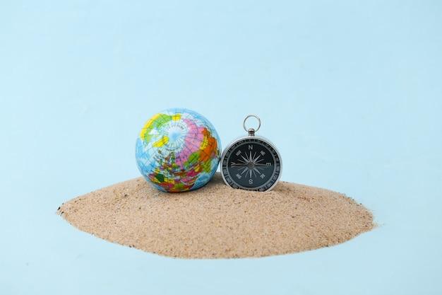 Boussole et globe sur un îlot de sable. voyage, concept d'aventure
