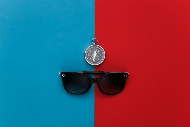 Boussole et lunettes de soleil sur un rouge-bleu