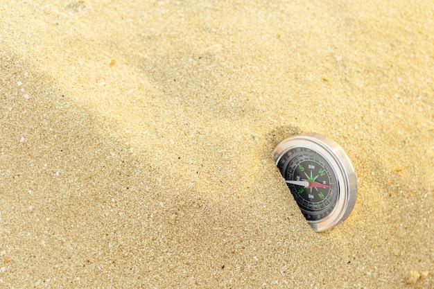 Boussole magnétique argentée sur fond de sable