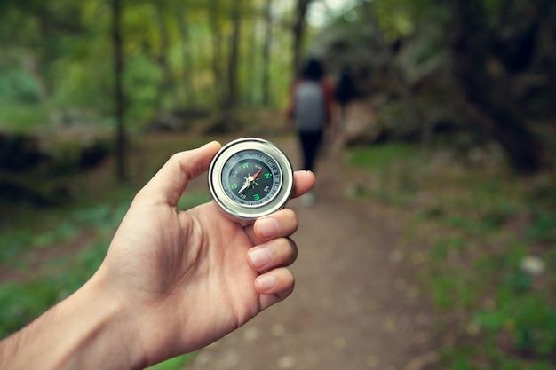 Boussole de main de l'homme dans le fond de la forêt