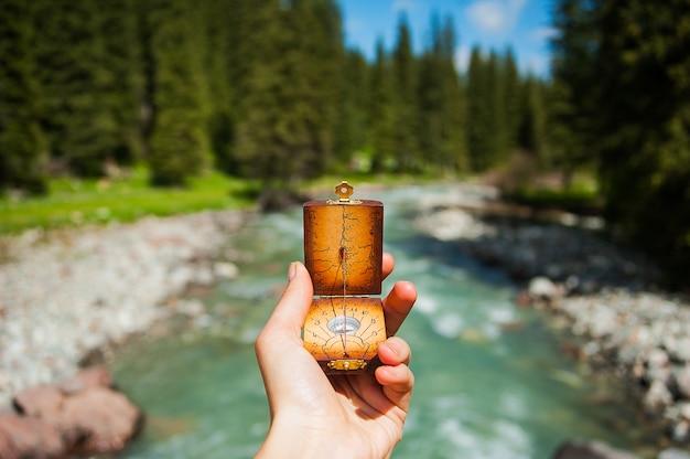 Boussole, mains, arrière-plan, rivière montagne