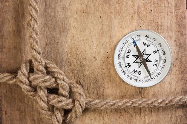 Boussole et noeud de corde sur un espace en bois