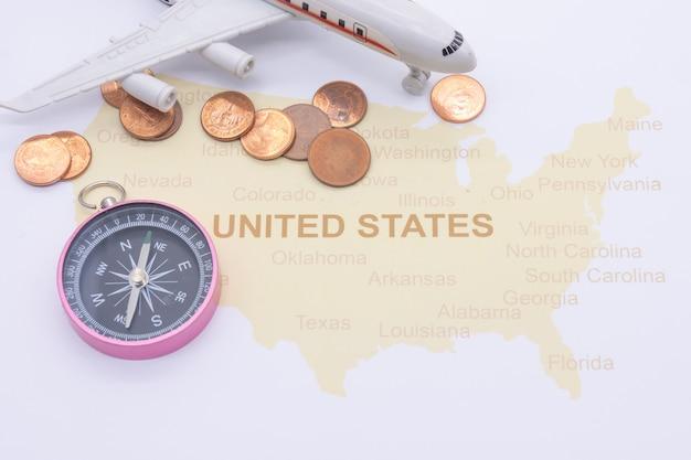 Boussole de passeport et pièces sur une carte américaine. concept de voyage d'affaires
