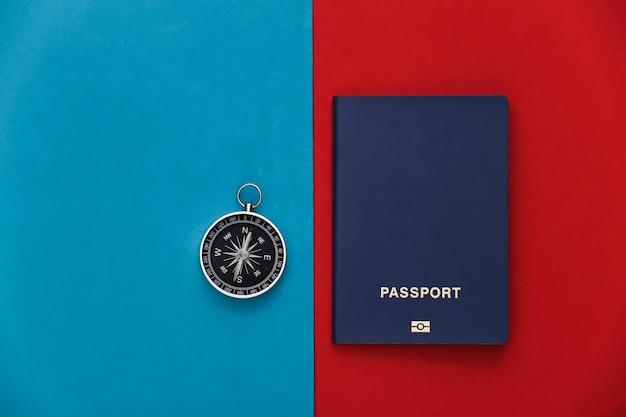 Boussole et passeport sur un rouge-bleu