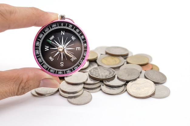 Boussole et pièces de monnaie sur fond blanc