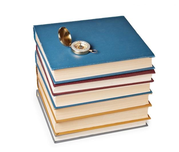 Boussole sur une pile de livres isolé sur fond blanc