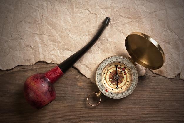 Boussole et une pipe à tabac sur une planche de bois, nature morte