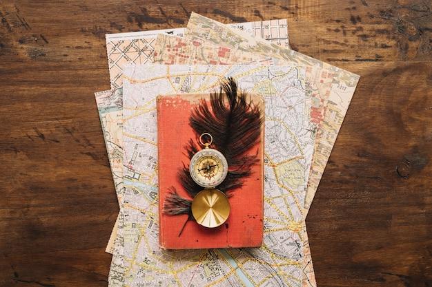 Boussole et plume sur le livre et les cartes