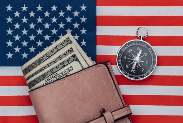 Boussole et sac à main sur le drapeau américain se bouchent. vue de dessus