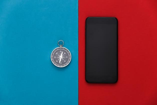 Boussole et smartphone sur un rouge-bleu