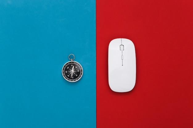 Boussole et souris pc sur un rouge-bleu. concept de voyage ou d'entreprise en ligne