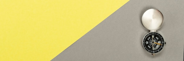 Boussole sur surface jaune gris, concept de voyage minimal