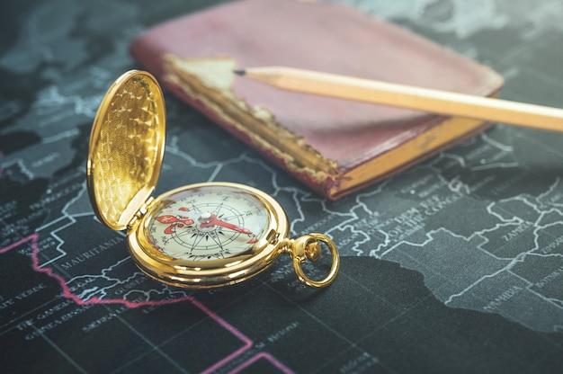 Boussole vintage, vieux cahier, crayon sur la carte du monde moderne