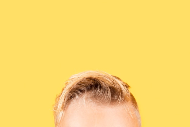 Bout de tête de garçon gros plan sur fond jaune