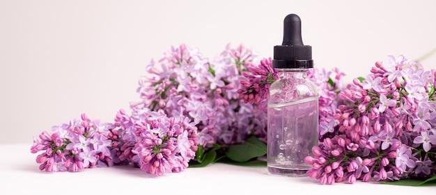 Bouteille d'acide hyaluronique et lilas sur fond blanc récipient de beauté soins de la peau v
