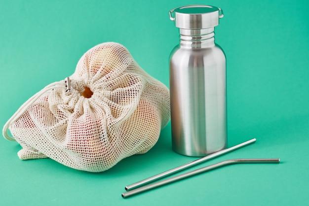 Bouteille en aluminium, tubes métalliques et fruits dans un sac naturel
