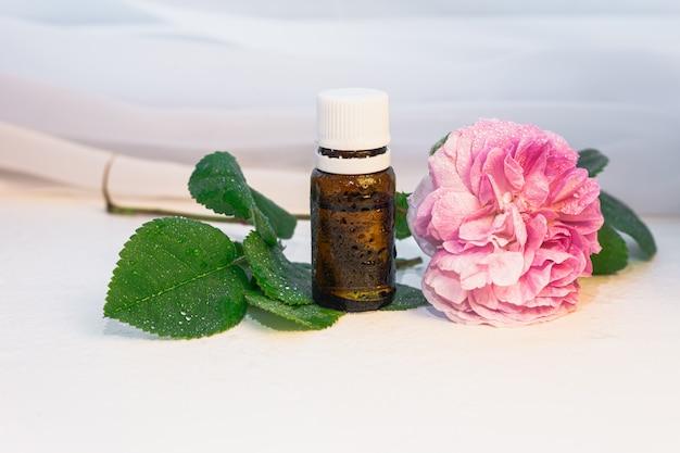 Bouteille ambrée d'huile essentielle avec espace de copie de fleur de rose produits de spa écologique concept de médecine naturelle
