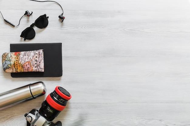 Bouteille, appareil photo, lunettes de soleil, écouteur et carte sur le journal sur le bureau en bois