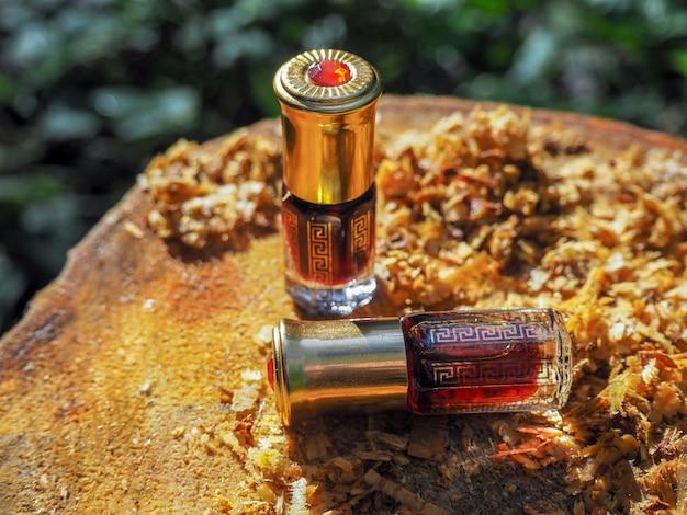 Bouteille d'arbre de bois d'agar contre l'écorce. oudh d'huile.