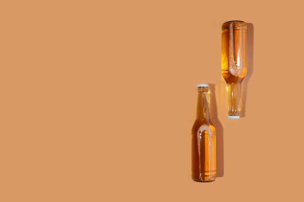 Une bouteille de bière artisanale sur fond beige. journée internationale de la bière ou concepts octoberfest.se reposer et boire de la bière après une dure journée de travail à la maison.couleurs minimalistes sur une photo. espace de copie
