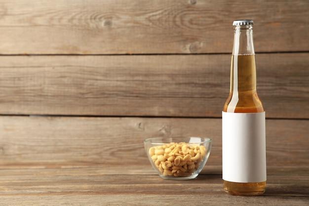 Bouteille de bière aux cacahuètes sur fond de bois gris. vue de dessus