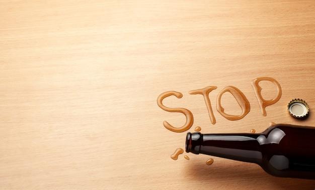 Bouteille de bière et bière renversée sous la forme du mot stop. interdire l'alcool.