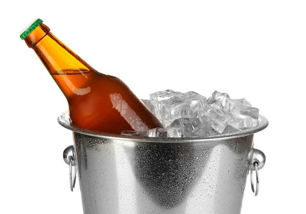 Bouteille de bière dans un seau à glace isolé sur blanc