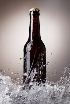 Bouteille de bière avec des éclaboussures d'eau