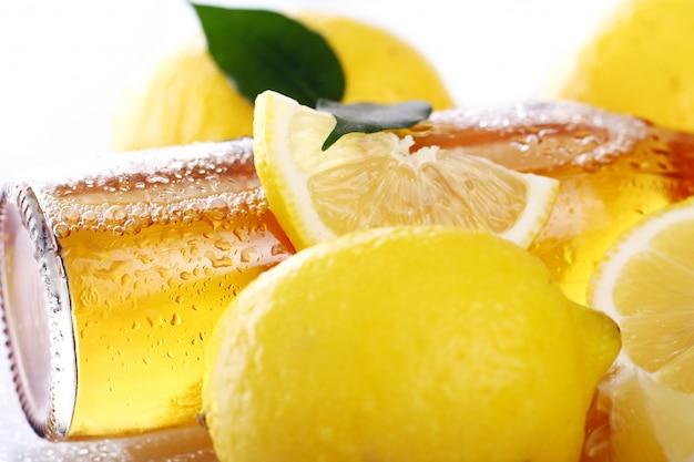 Bouteille de bière froide avec des citrons frais