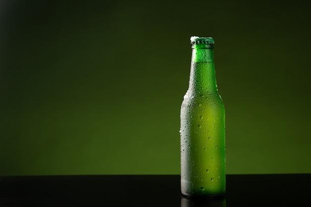 Bouteille de bière froide avec goutte d'eau sur fond vert avec copyspace.