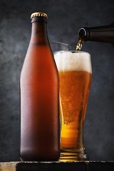 Bouteille de bière légère et un verre plein de boisson sur une table en bois