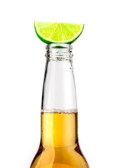 Bouteille de bière mexicaine avec tranche de citron vert et givre sur fond blanc