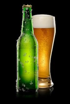 Bouteille de bière verte avec des cristaux de glace et un verre de bière sur fond noir.