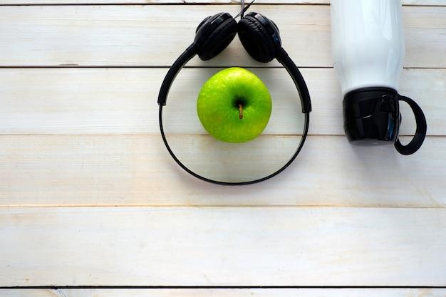 Bouteille blanche, casque et pomme verte sur la vue de dessus de planche de bois blanc pour l'espace