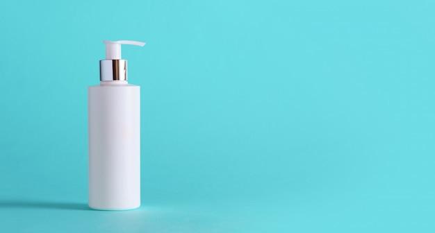 Bouteille blanche de lotion hydratante sur fond bleu avec espace de copie.