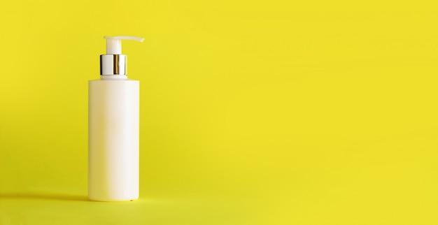 Bouteille blanche de lotion hydratante sur fond jaune avec espace de copie