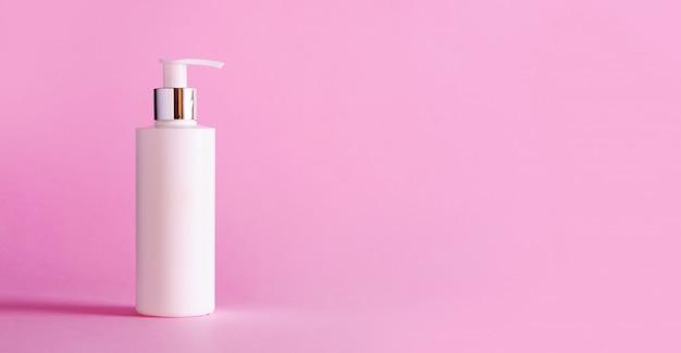 Bouteille blanche de lotion hydratante sur fond rose avec espace de copie