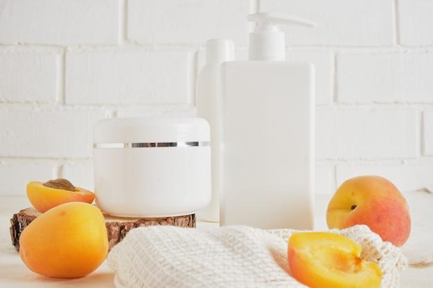 Bouteille blanche en plastique d'abricots avec un distributeur de crème ou de savon, un podium en bois d'une scie coupée d'un arbre sur une vue de dessus de fond clair