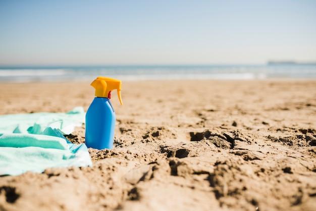 Bouteille bleue de lotion écran solaire sur la plage de sable fin