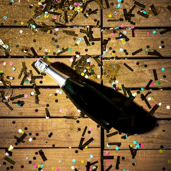 Bouteille de boisson entre confettis brillants