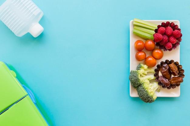 Bouteille et boîte à lunch près de la nourriture saine