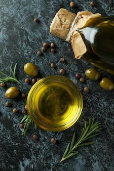 Bouteille et bol avec de l'huile d'olive et des épices sur fond noir fumé