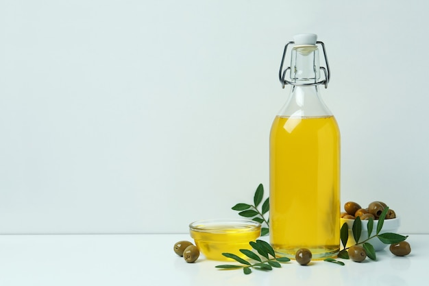 Bouteille et bol d'huile d'olive, olives et brindilles sur blanc