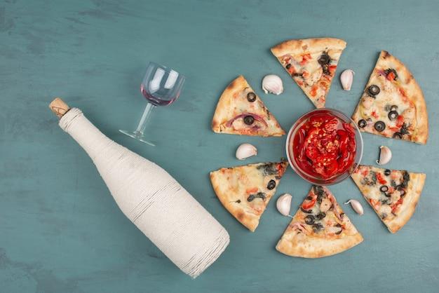 Une bouteille, un bol de poivron rouge mariné, des tranches de pizza sur une surface bleue.