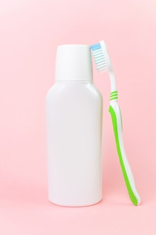 Bouteille et brosse à dents blanches en rose pastel.